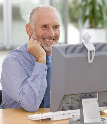 Businessman Smiling And Looking At Computer Monitor